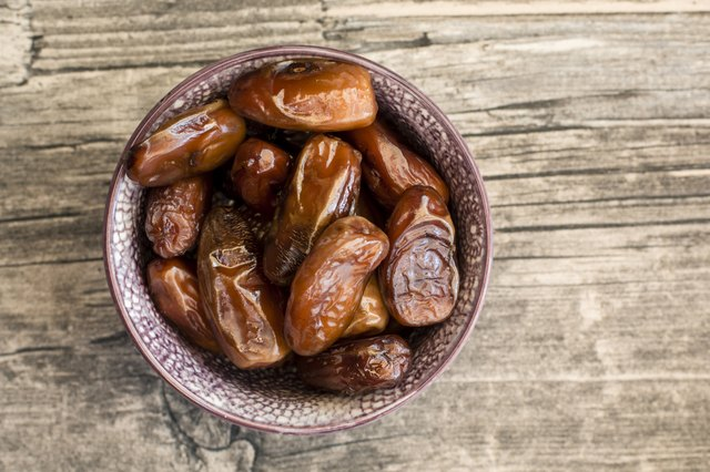 Bowl of dates on wood