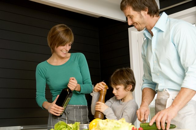 Mid adult man and a young woman preparing food with their son in a kitchen
