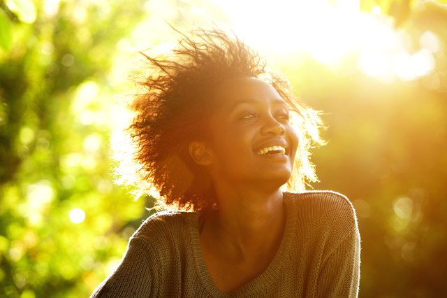 Beautiful african american woman smiling with sunset