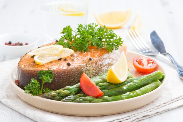 baked salmon with asparagus and lemon on plate