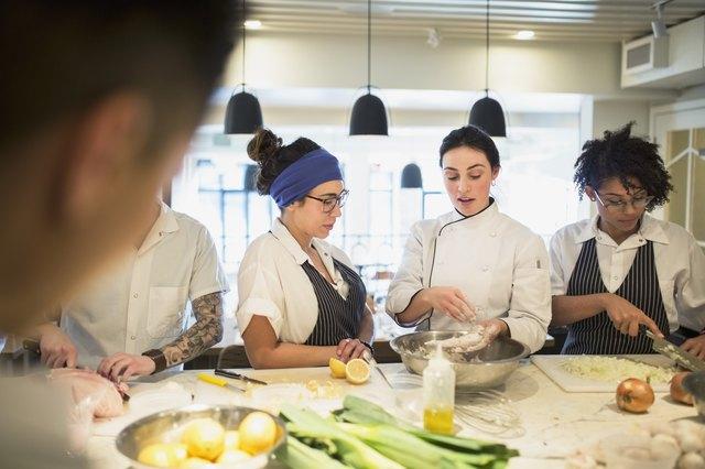 Chef mentoring students in restaurant kitchen