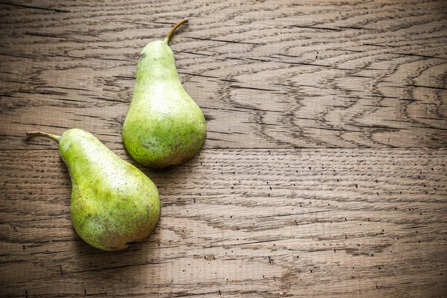 Halves of green pear on the wooden background