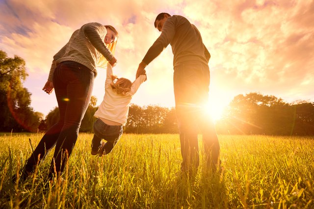 Parents hold baby's hands.  Happy family in park evening