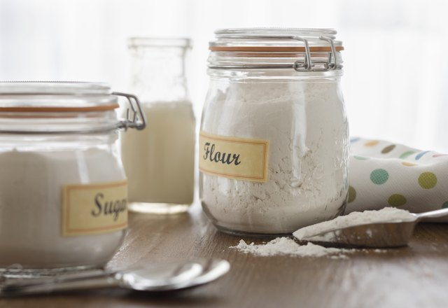 Glass jars of sugar, cream, and flour on counter