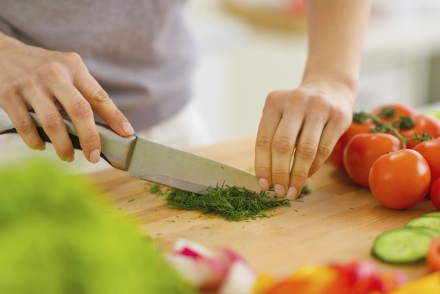 Closeup on woman cutting fresh dill
