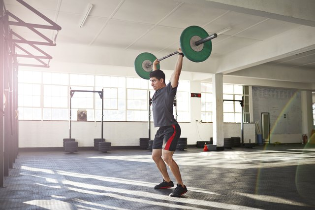 Crossfit instructor lifting barbell at urban gym