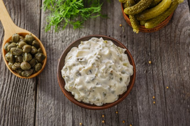 tartar sauce in a gravy boat on a wooden surface