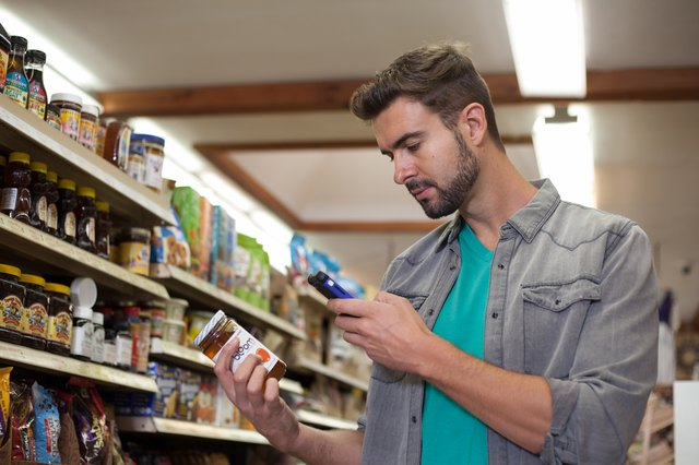 Young man checking product on smartphone in health food store
