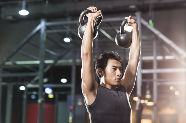 Young man training with kettlebells in crossfit gym