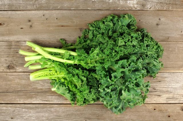 Bunch of fresh green kale over an aged wooden background. Overhead view.