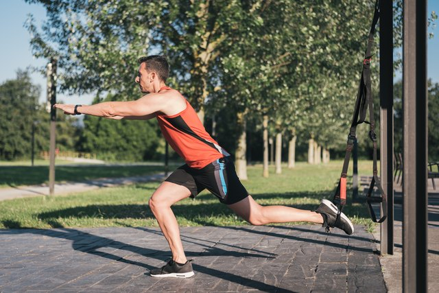 Man doing leg lunges training with trx fitness straps outdoor