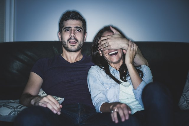Couple watching thriller on sofa