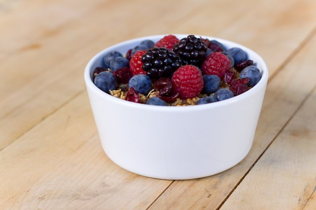 bowl of fruit and Granola on wooden table