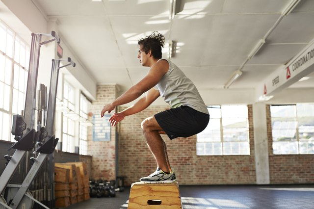 Man doing box jump in crossfit gym