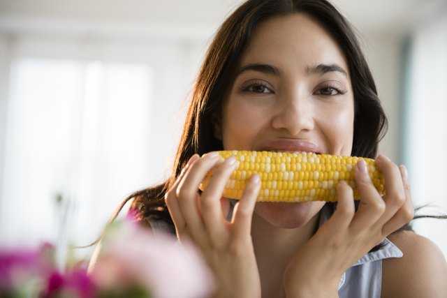 Hispanic woman eating corn on the cob