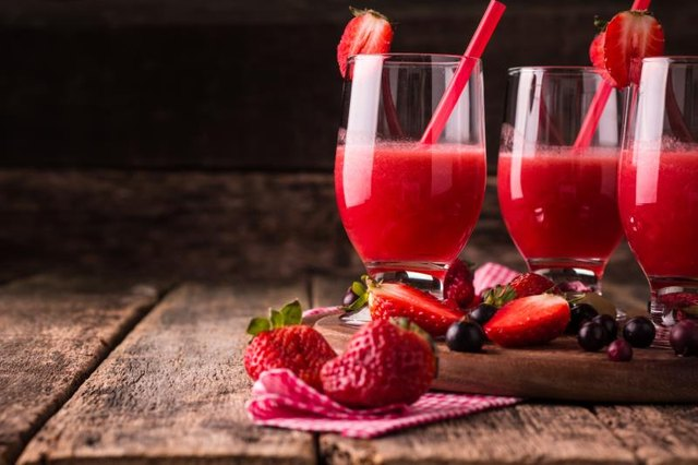 Glasses of fresh cold smoothie with fruit and berries, on wooden background, healthy detox drink