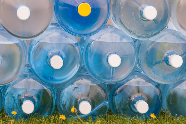 Water Jugs Stacked on Grass