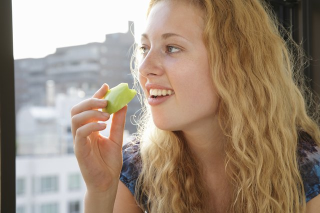 Young woman holding a slice of apple