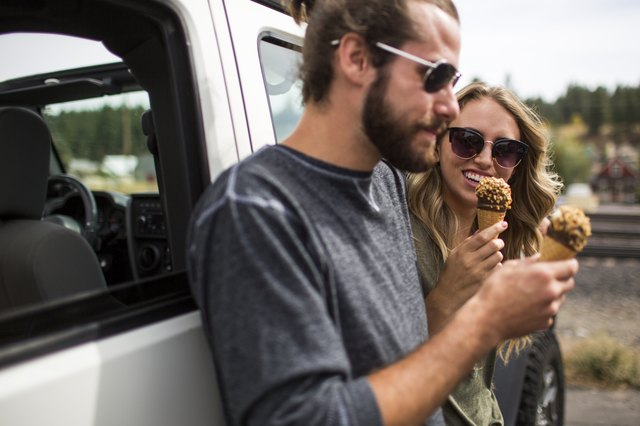 Young couple leaning against jeep eating ice cream cones