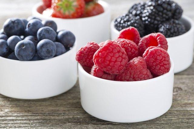 fresh raspberries in a bowl and berries, closeup, horizontal