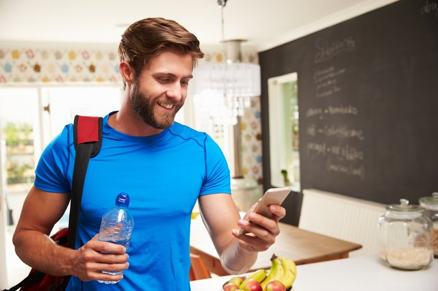 Man wearing gym gear holding a bottle of water in a kitchen