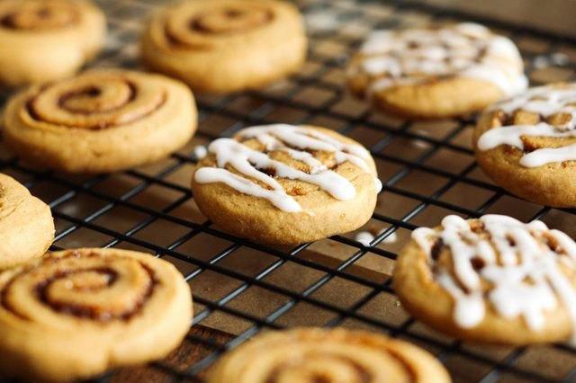Freshly baked sweet potato cinnamon roll cookies sitting on a wire rack.