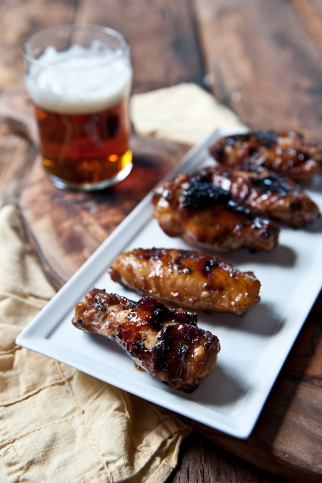 Dish with honey stout chicken wings with a glass of beer.