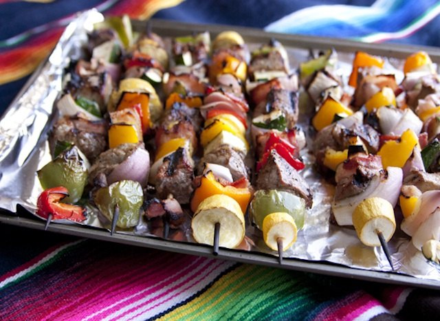 Grilled steak and bacon shish kebabs with peppers and onion on baking sheet.