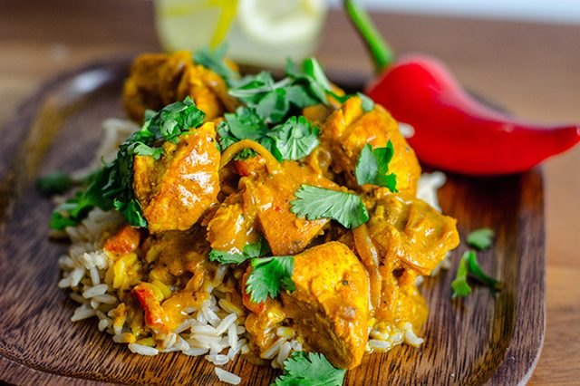 A plate of bright orange curry on a bed of rice.