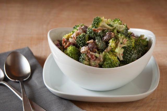 Broccoli bacon raisin salad in white bowl.