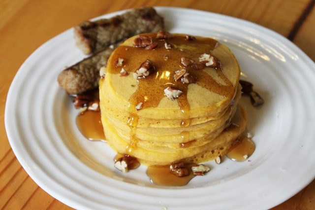 A stack of orange-hued pumpkin pancakes topped with pecans and maple syrup, served with two sausage links.
