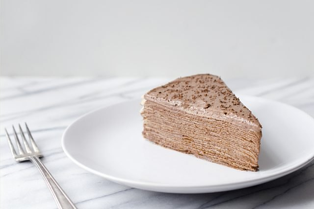 A fluffy, light brown Nutella crepe cake slice.