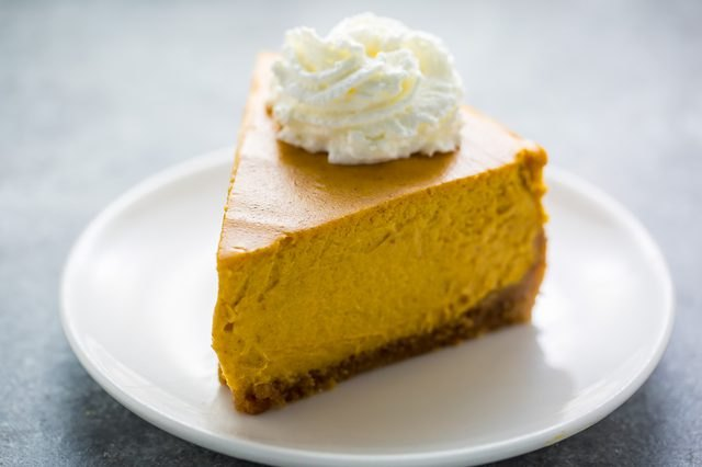 A slice of pumpkin cheese cake topped with whipped cream