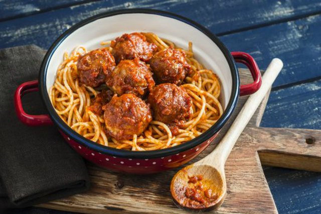Spaghetti and meatballs in tomato sauce on wooden rustic board
