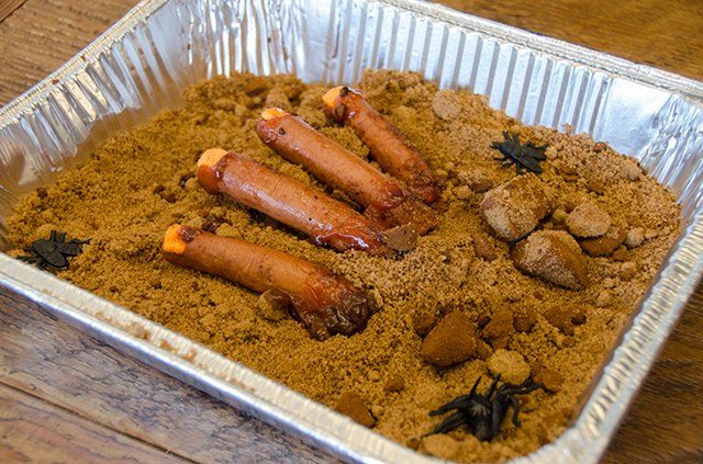 Cooked hot dogs on a bed of brown sugar that looks like sand and dirt.