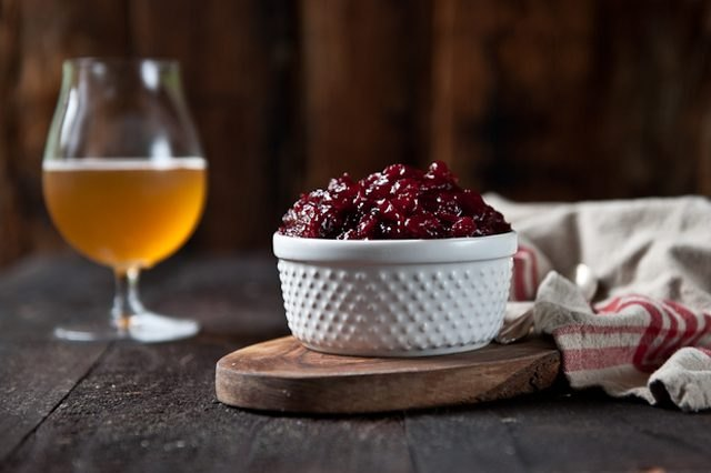 A dish filled with orange winter ale cranberry sauce, served with a beer.