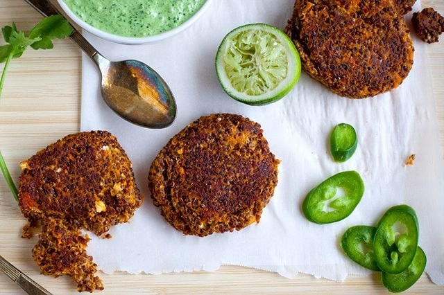 Sweet potato chipotle quinoa cakes on a cutting board with limes, sliced jalapenos and cilantro lime crema.