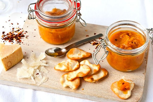 Jars of English peach and ginger chutney on wooden board with Parmesan and chips.