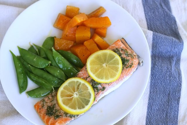 Salmon served with dill, butternut squash and sugar snap peas