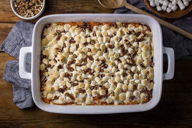 A large sweet potato casserole topped with pecans and marshmallows