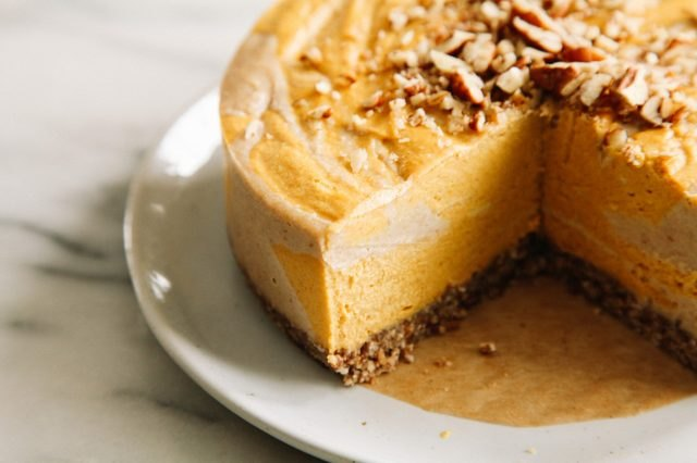 A bright orange raw pumpkin swirl cheesecake topped with pecans.