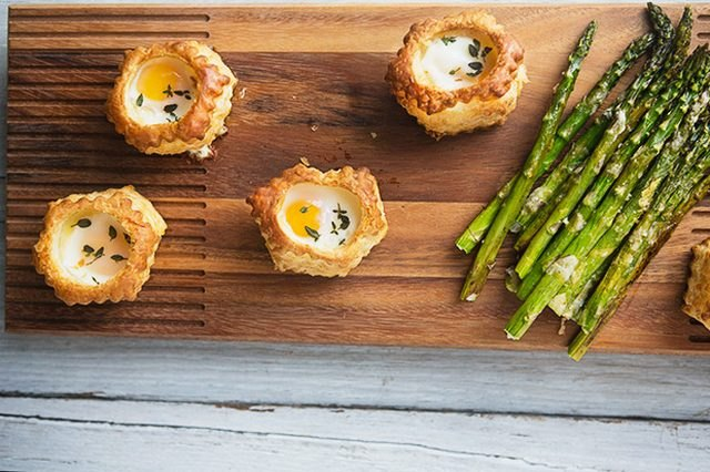 Four parmesan and thyme pastry baked eggs with a side of asparagus.