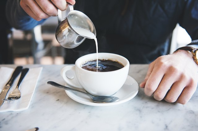 A man pours cream into his coffee