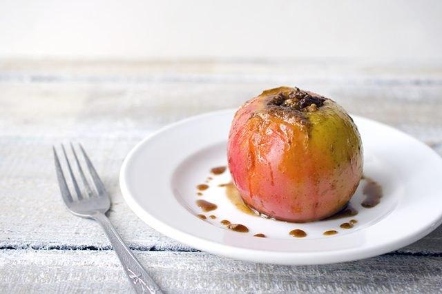 A freshly baked pecan-stuffed apple on a plate.