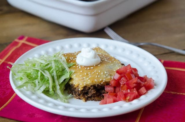 A baked taco square beside shredded lettuce, diced tomatoes and a dollop of sour cream.