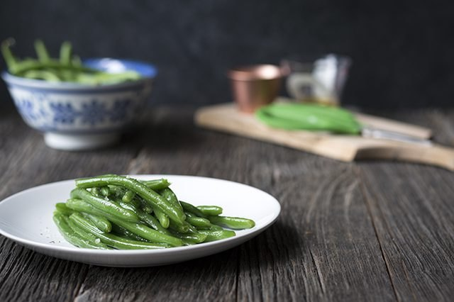 A plate of green beans in the foreground and a bowl of uncooked green beans in the background
