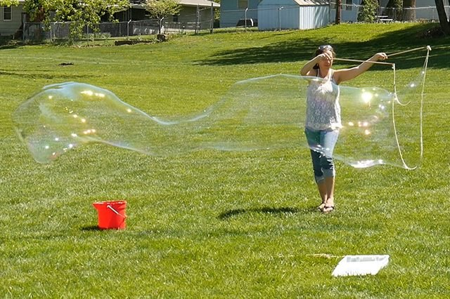 A woman on a lawn making a giant bubble with a bubble wand