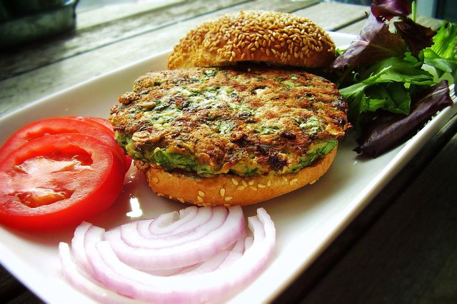 Side view of a spinach-stuffed turkey burger on a bun with tomato and onion
