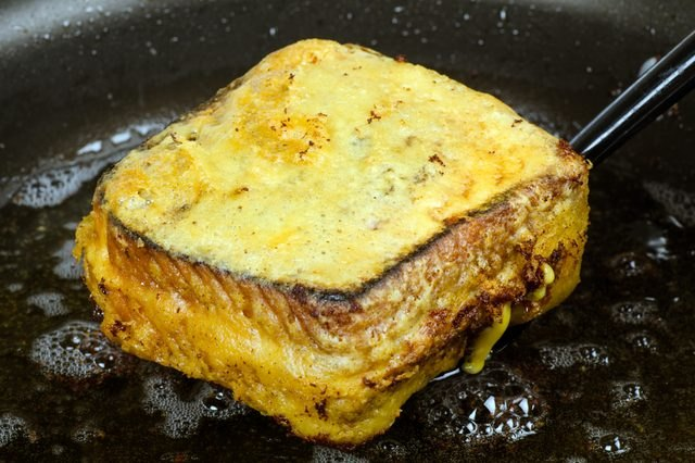 A freshly deep-fried grilled cheese sandwich emerging from hot oil.