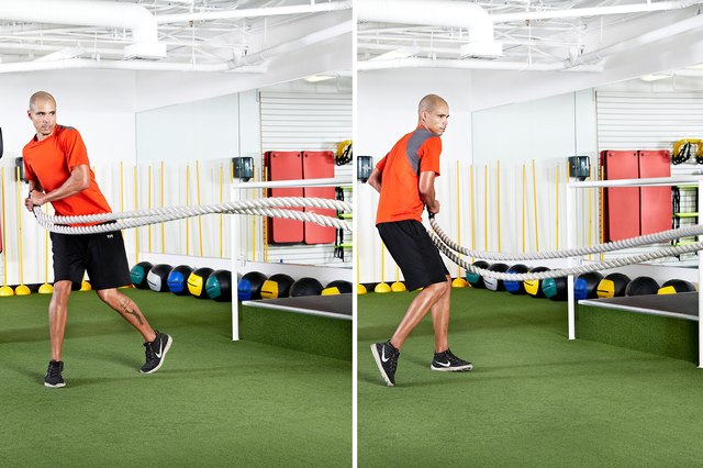 Man doing standing hip-toss rotations with the battle ropes